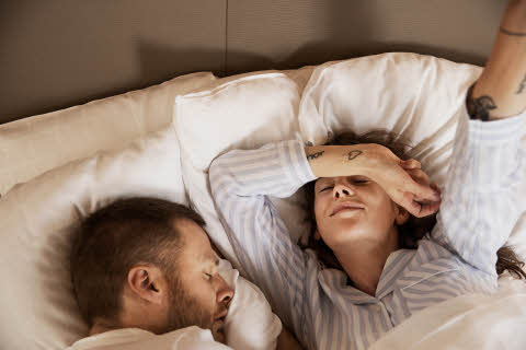 Couple in bed sleeping in hotel room at scandic hotels