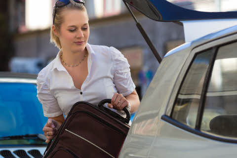 7136753-woman-loads-suitcase-into-car-boot-or-trun.jpg