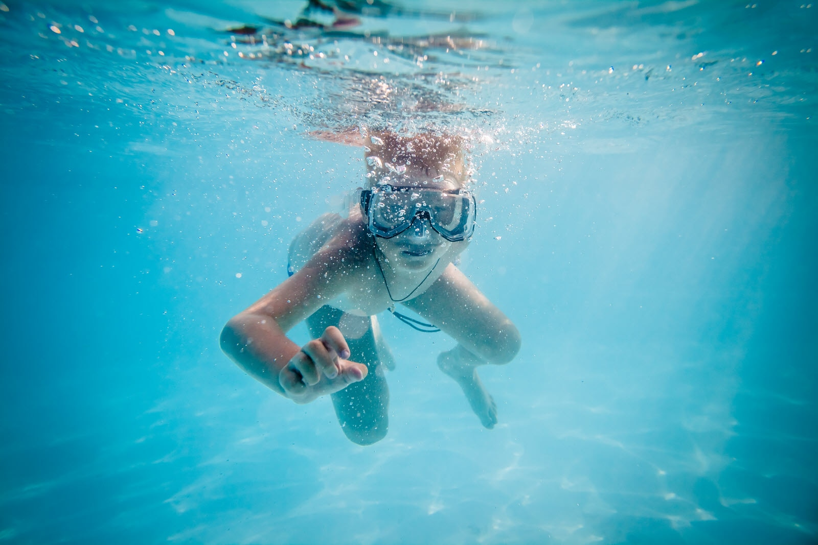 Boy swimming under water in pool